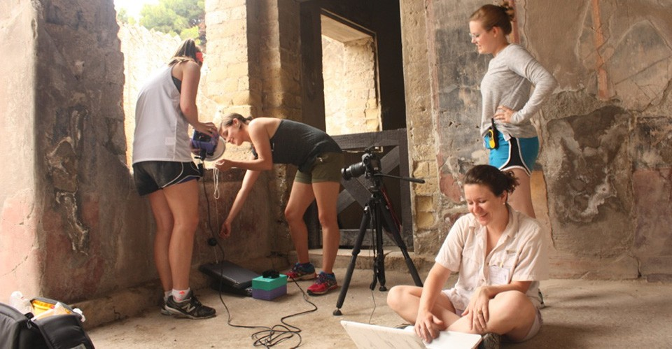 Jacqueline DiBiasie (seated) works with students, including Grace Gibson, C'17, (center) to document ancient graffiti inscribed in the plaster of Herculaneum.