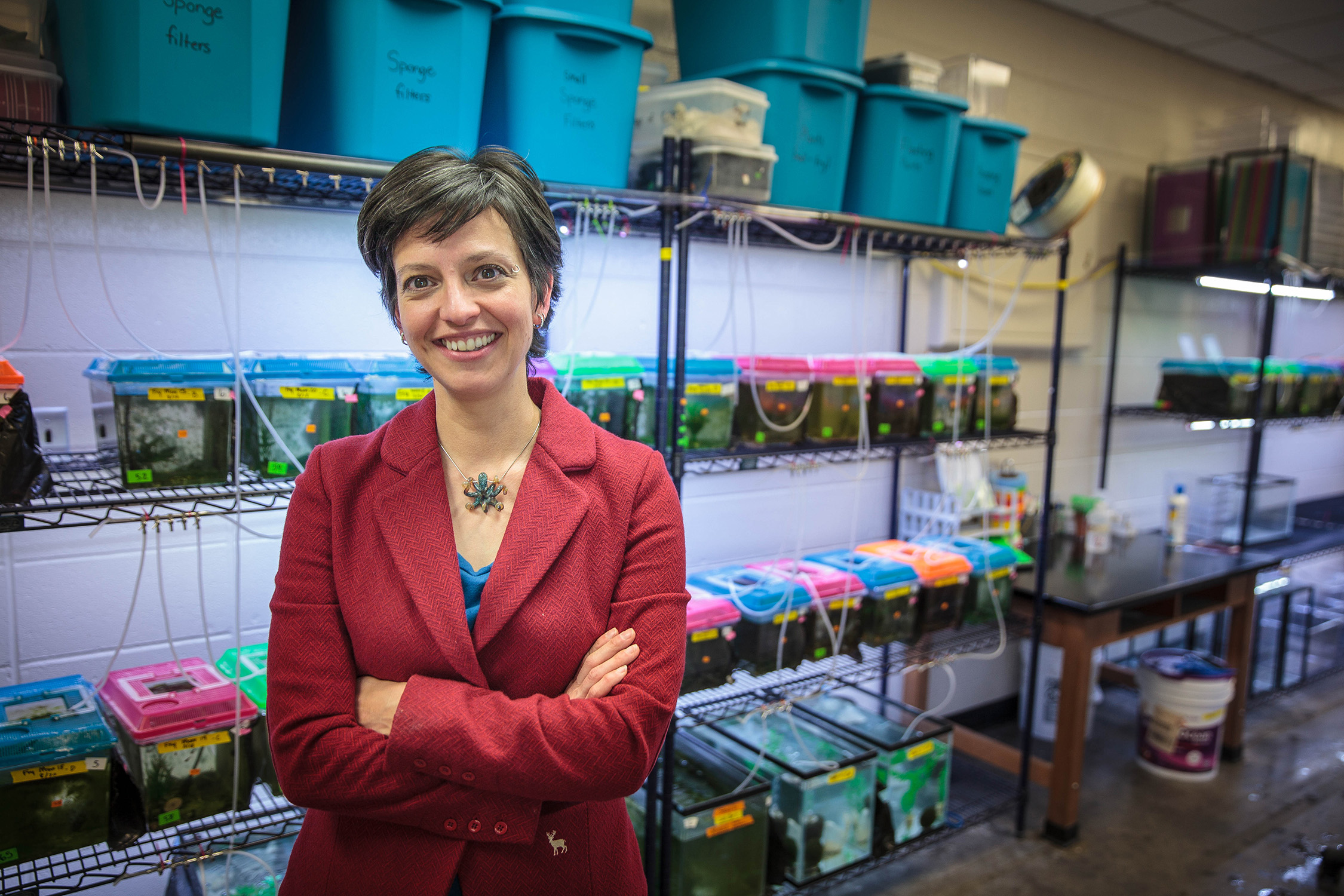 Assistant Professor of Biology Katie McGhee with her fish tanks in Woods Labs. Photo by Buck Butler
