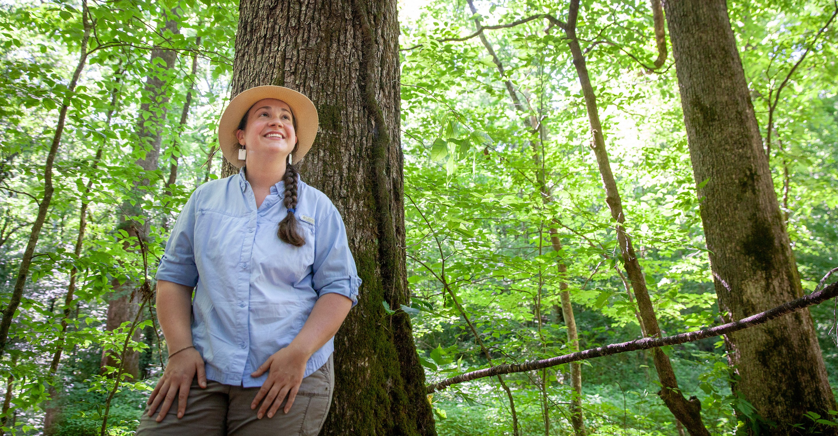 Alex Richman, C'05, among the white oaks on the family land she manages in Moore County, Tennessee. Photo by Buck Butler
