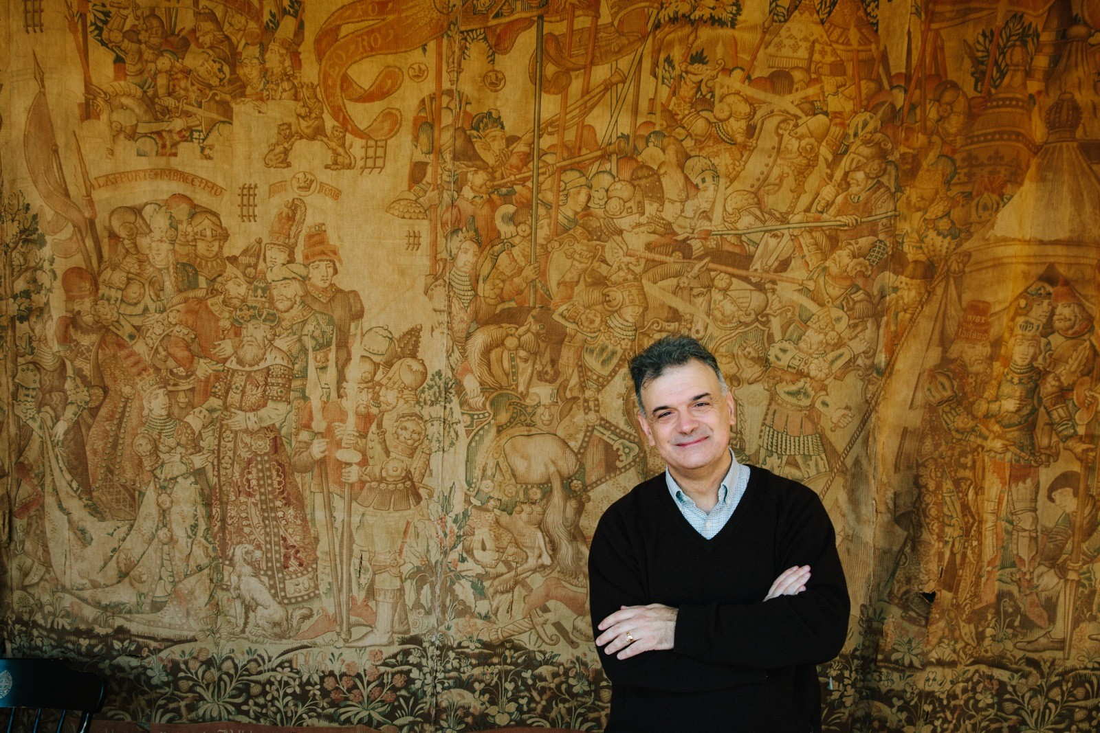 Classics Professor Chris McDonough surrounded by scenes from the Trojan War, depicted in what may be a 19th-century reproduction of a 15th-century Belgian tapestry that hangs in the McGriff Alumni House.