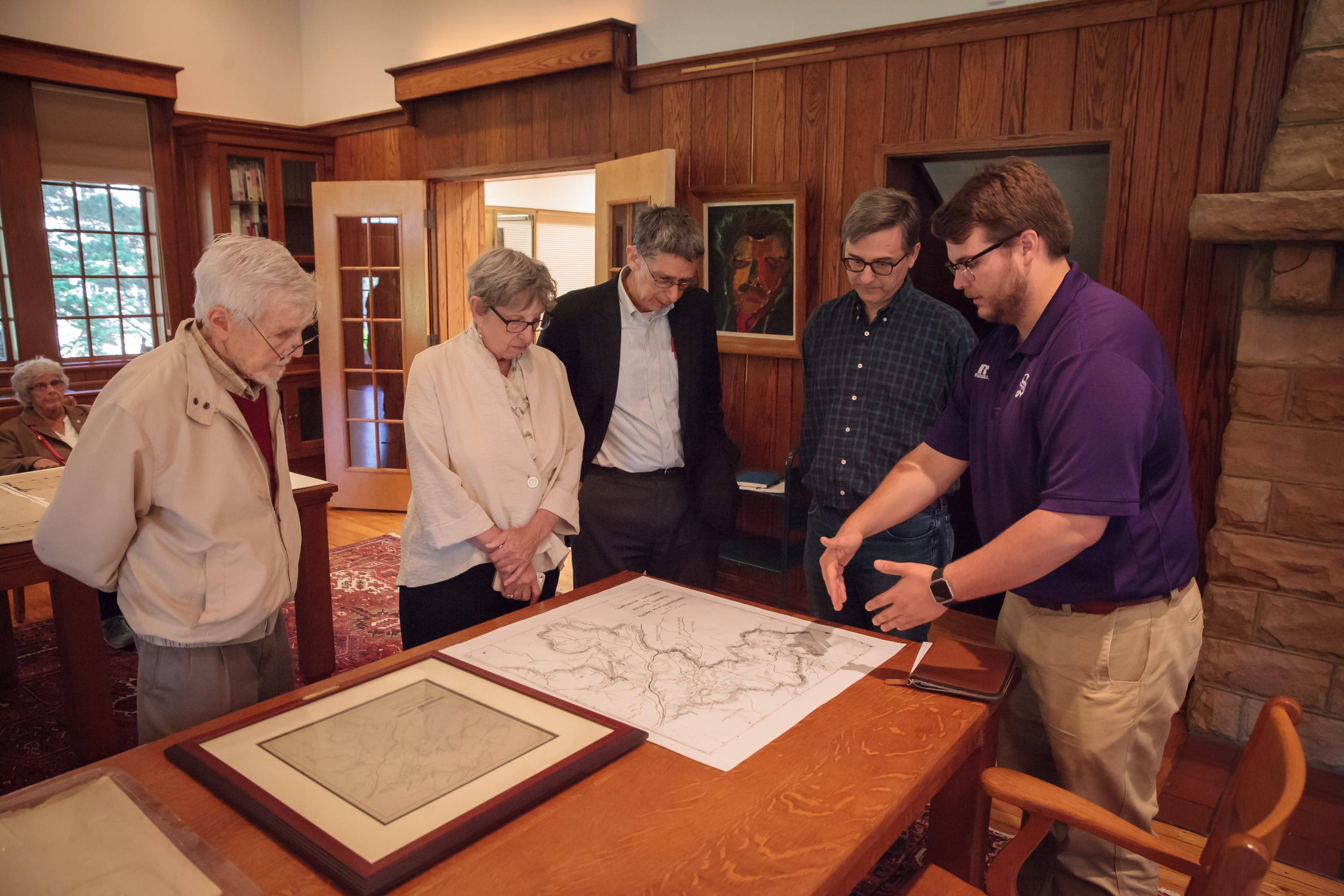 Susanna Grannis and Tom Whitney examine a founding-era map of the Domain with Woody Register and Tanner Potts during a visit to University Archives.