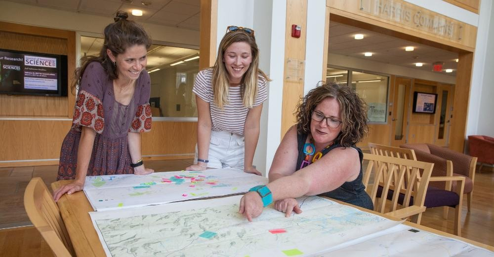 Anna Sumner Noonan C'17, Catherine Casselman, C'17, and Margo Shea pore over maps of the South Cumberland Plateau annotated with local residents' stories about places that are significant to them. Photo by Buck Butler
